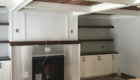 built in white cabinets with dark stained shelves and mantel